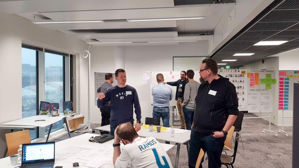 Ryhmä miehia suunnittelee Kalasatamaa neuvotteluhuoneessa
