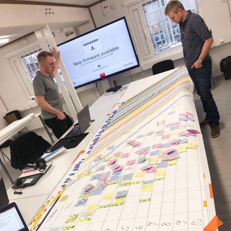 Miehet tutkivat Last Planner suunnitelmaa neuvotteluhuoneessa